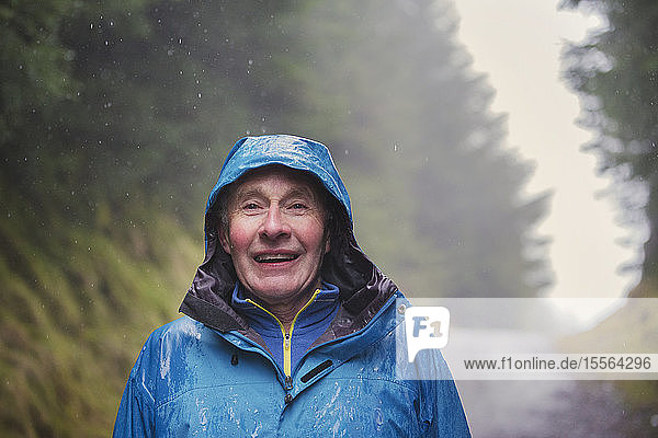 Portrait senior man hiking in rain