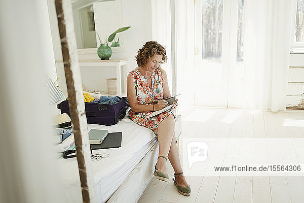 Woman writing in journal next to suitcase on beach hut bedroom
