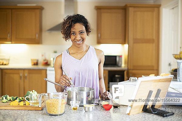 Portrait confident woman cooking in kitchen