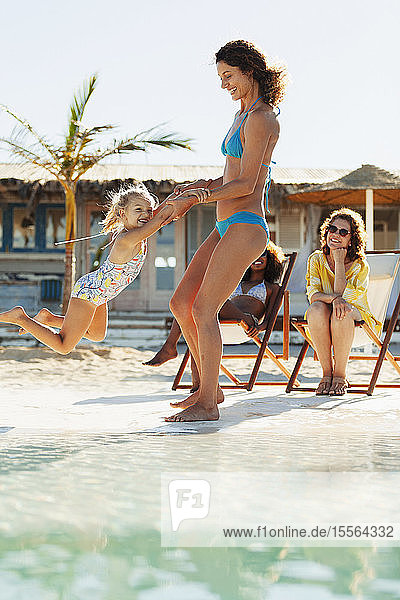 Playful mother and daughter on sunny beach