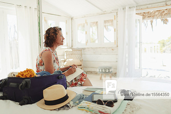 Serene woman writing in journal next to suitcase in beach hut bedroom