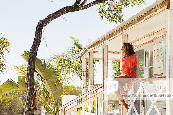 Young  serene woman relaxing on sunny beach hut patio