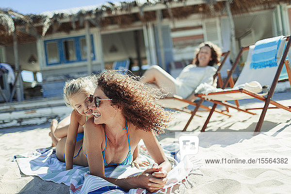 Happy mother and daughter on sunny beach