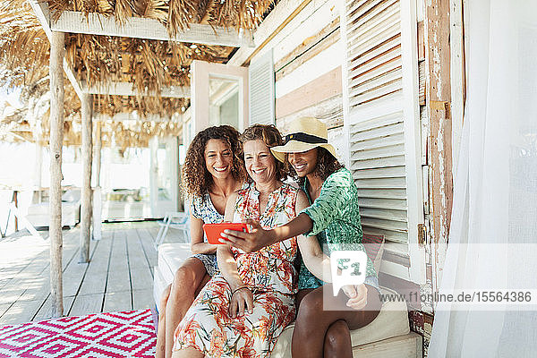 Happy mother and adult daughters taking selfie on beach hut patio