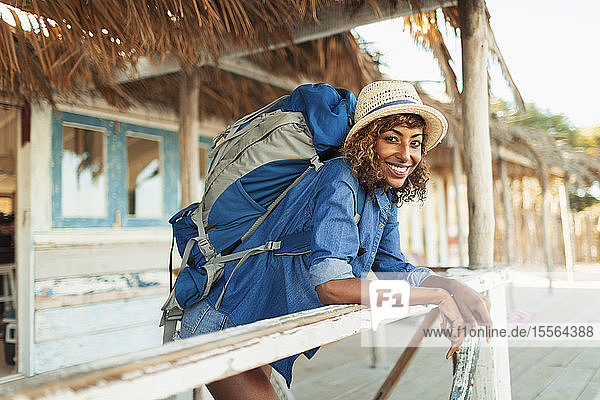 Portrait happy young female backpacker on beach hut patio