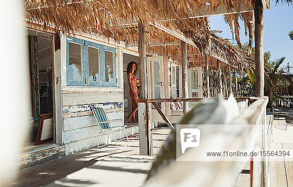 Woman in bikini standing in doorway of sunny beach hut