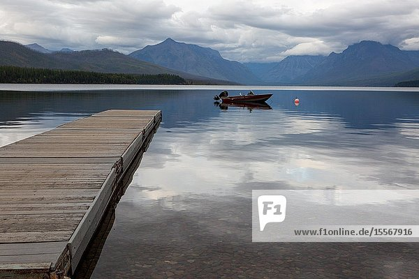 A boat rests at anchor in the evening calm waters of Lake McDonald in Glacier National Park  in Montana.