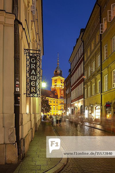 Evening in Warsaw old town  Poland. Royal Castle tower in hte distance.