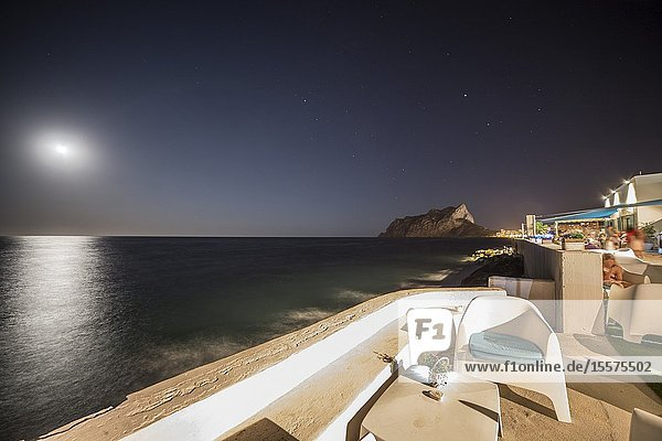 Benissa Alicante Spain on August 15  2019: Bassetes cove with beach club and Penyon de Ifach rock in Calp Mediterranean coast with full moon.