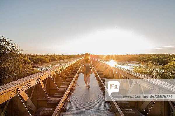 A happy young slender girl walks near a bridge in the rays of the summer sun. sunset on a summer day.