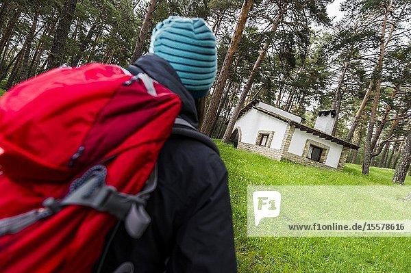 Young hiker walking towards mountain refuge in Iberian Mountain Range (Guadalajara province  Castilla-La Mancha Region  Spain)