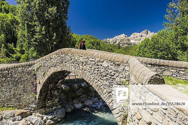 Young hiker crossing the old bridge of Bolática River  Panticosa  Tena Valley  Pyrenees (Huesca province  Aragón  Spain)