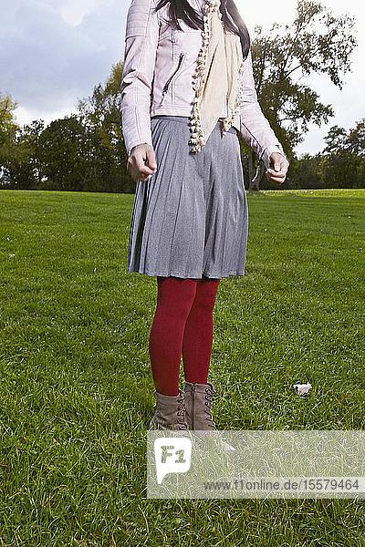 Deutschland  Köln  Junge Frau steht auf Gras im Park