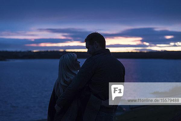 Ein Paar beobachtet den Sonnenuntergang am See