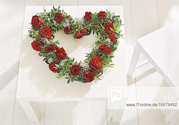 Herzförmiger Blumenkranz auf Tisch zum Muttertag