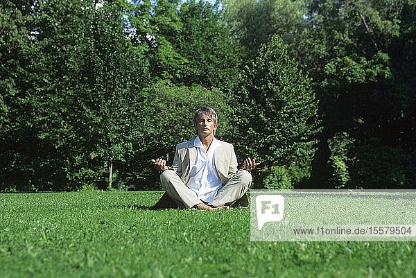 Mittelgroßer  meditierender Mann im Park  Bodenansicht