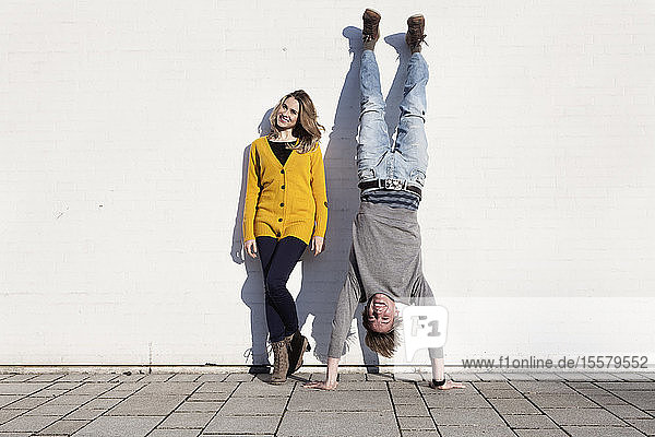 Germany  Bavaria  Munich  Young couple against wall  smiling