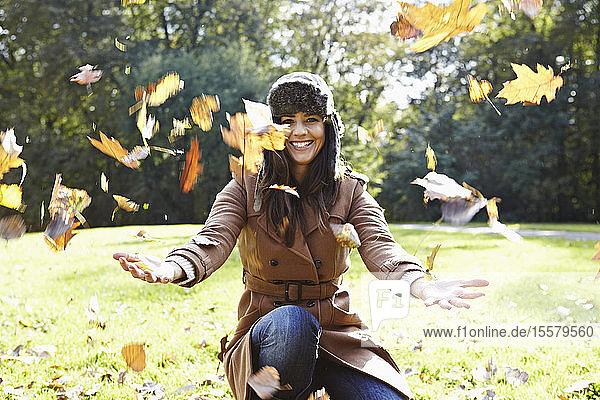 Deutschland  Köln  Junge Frau spielt im Park mit Blättern  lächelnd  Porträt