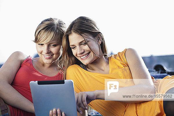 Deutschland  Köln  Junge Frau mit digitalem Tablet  lächelnd