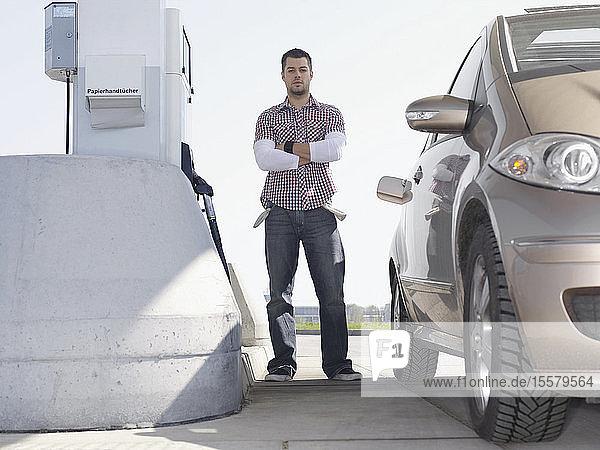 Deutschland  Augsburg  Junger Mann mit leeren Taschen mit dem Auto an der Tankstelle