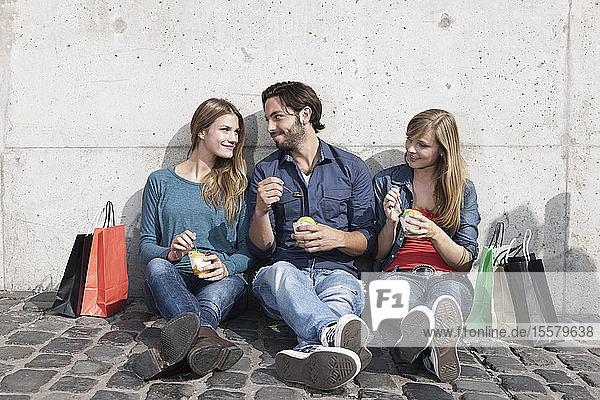 Deutschland  Köln  Junger Mann und Frau mit Eis und Einkaufstaschen  lächelnd