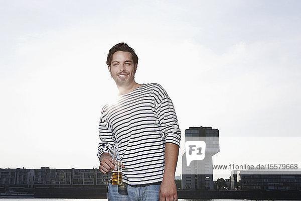 Deutschland  Köln  Junger Mann mit Bierflasche  lächelnd  Porträt