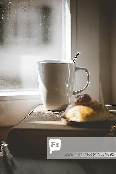 Becher Kaffee mit Brioche auf altem Buch