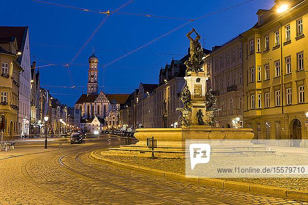 Deutschland  Bayern  Augsburg  Herkulesbrunnen  Maximilianstraße zur blauen Stunde  Basilika der SS. Ulrich und Afra im Hintergrund