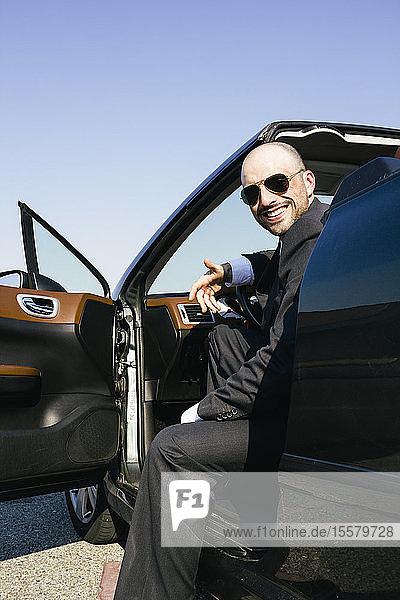 Geschäftsmann mit Sonnenbrille lächelnd in einem Cabriolet sitzend