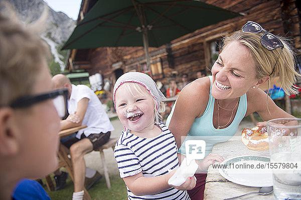 Fröhliches kleines Mädchen isst Kuchen mit der Familie in der Alphütte