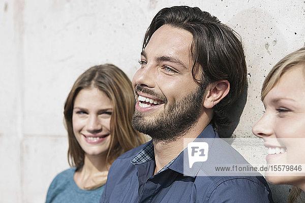 Deutschland  Köln  Junger Mann und Frau an Wand gelehnt  lächelnd