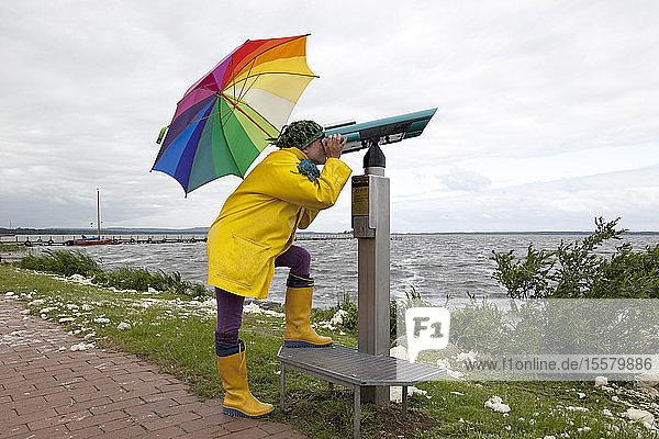 Deutschland  Steinhuder Meer  Frau in gelben Wellington-Stiefeln und Regenmantel schaut durchs Teleskop