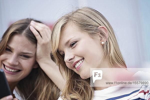 Deutschland  Köln  Junge Frau mit Handy  lächelnd