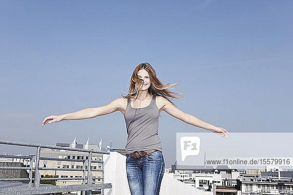 Deutschland  Köln  Junge Frau am Parkhaus  lächelnd  Porträt