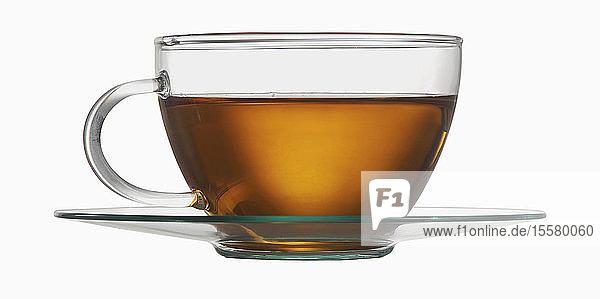 Teetasse aus Glas mit Tee auf weißem Hintergrund,  Nahaufnahme