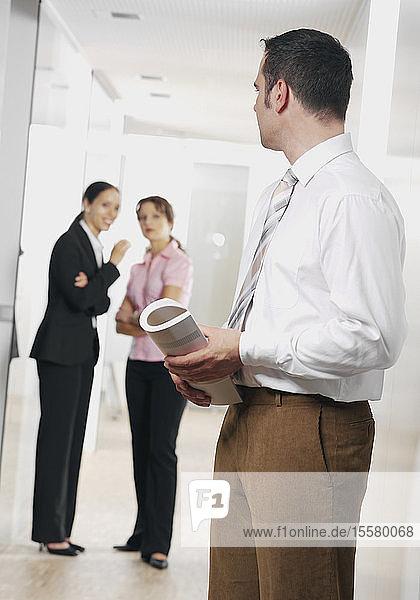 Junge Geschäftsfrau flüsternd und Geschäftsmann listnen