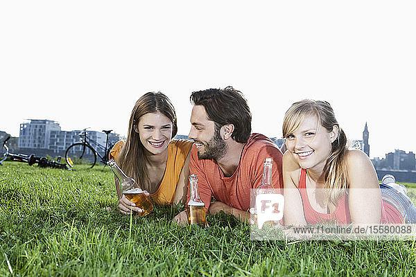 Deutschland  Köln  Junger Mann und Frau liegen mit Bierflaschen im Gras und lächeln