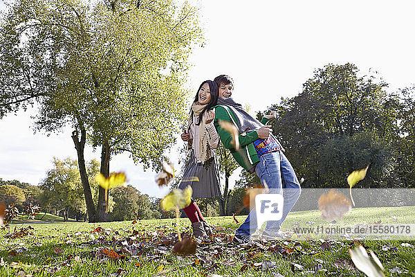 Deutschland  Köln  Junges Paar im Park  lächelnd  Porträt