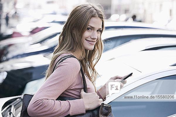 Deutschland  Köln  Junge Frau mit Telefon in der Nähe des Parkplatzes  lächelnd  Porträt