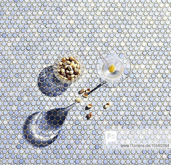 Direkt darüber Schuss Pistazien und Martini-Glas auf blau gemustertem Hintergrund