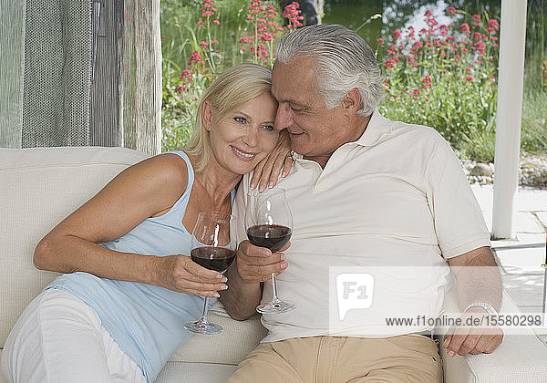 Deutschland  München  Seniorenpaar zu Hause auf dem Sofa
