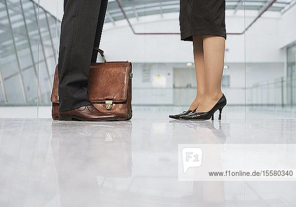 Geschäftsleute stehen auf glänzendem Boden