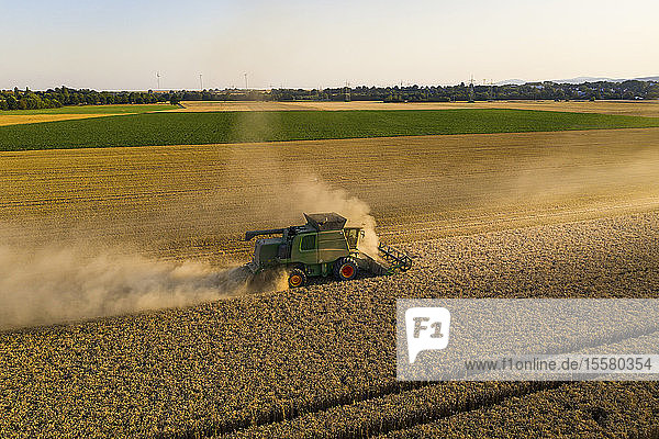 Aerial view of combine harvester on agricultural field against clear sky during sunset