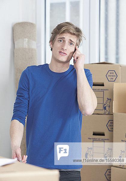 Junger Mann spricht mit dem Handy  bewegt Lagerboxen