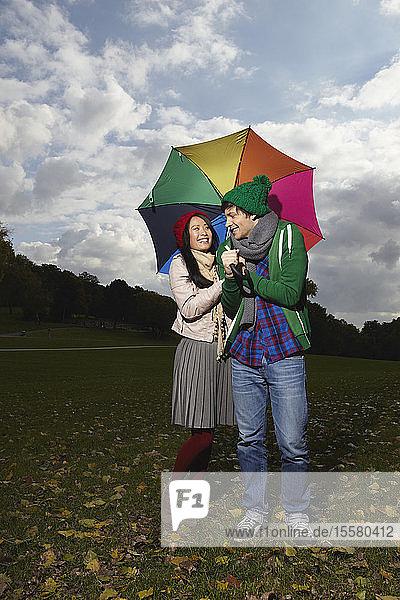 Deutschland  Köln  Junges Paar mit Regenschirm im Park  lächelnd