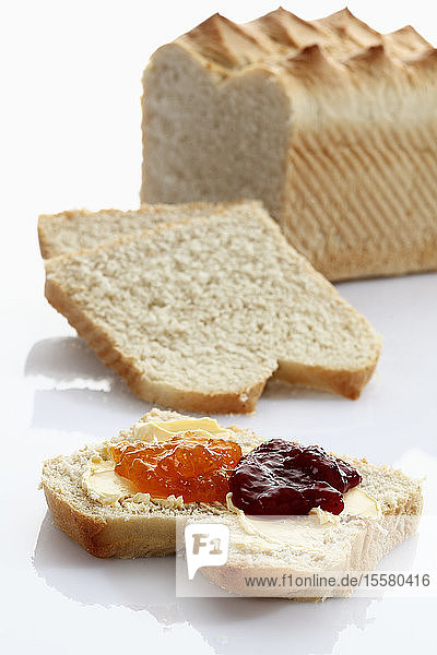Weißbrotscheibe mit Butter und Marmelade auf weißem Hintergrund
