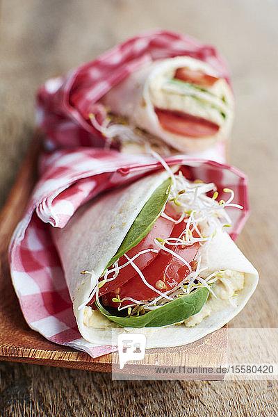 Tortilla wickelt mit Humus  Blattspinat  Sprossen und Tomatenscheiben auf Holzbrett Tortilla wickelt mit Humus, Blattspinat, Sprossen und Tomatenscheiben auf Holzbrett