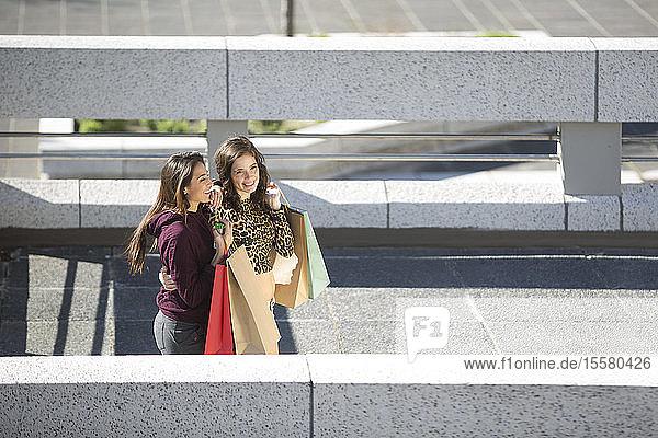 Zwei glückliche Freundinnen mit Einkaufstaschen