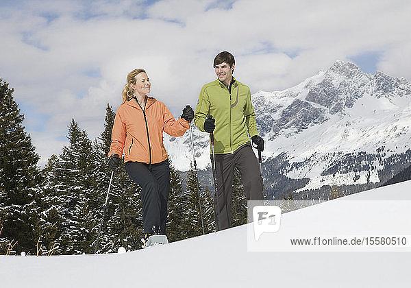 Deutschland  Bayern  Junger Mann und Frau gehen im Schnee
