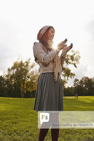 Deutschland  Köln  Junge Frau mit Handy im Park